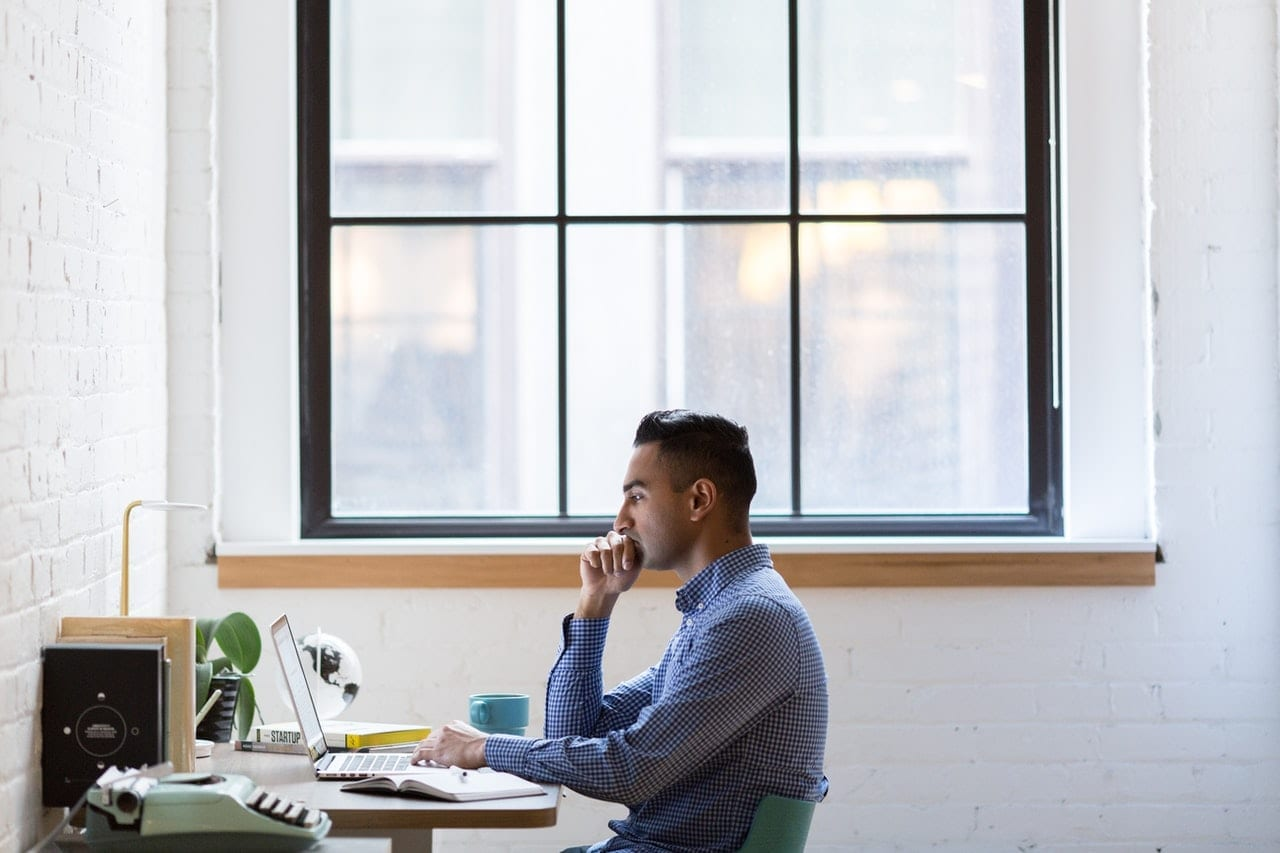 man wearing gray long sleeved shirt wants to create a website on his computer