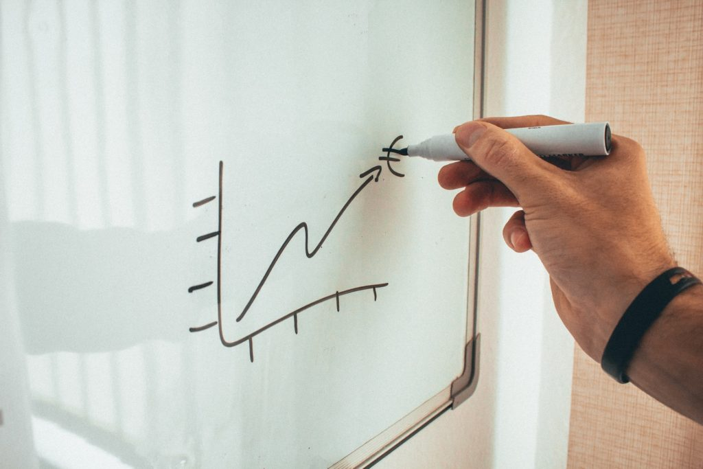Man drawing on whiteboard to illustrate benefits of remarketing